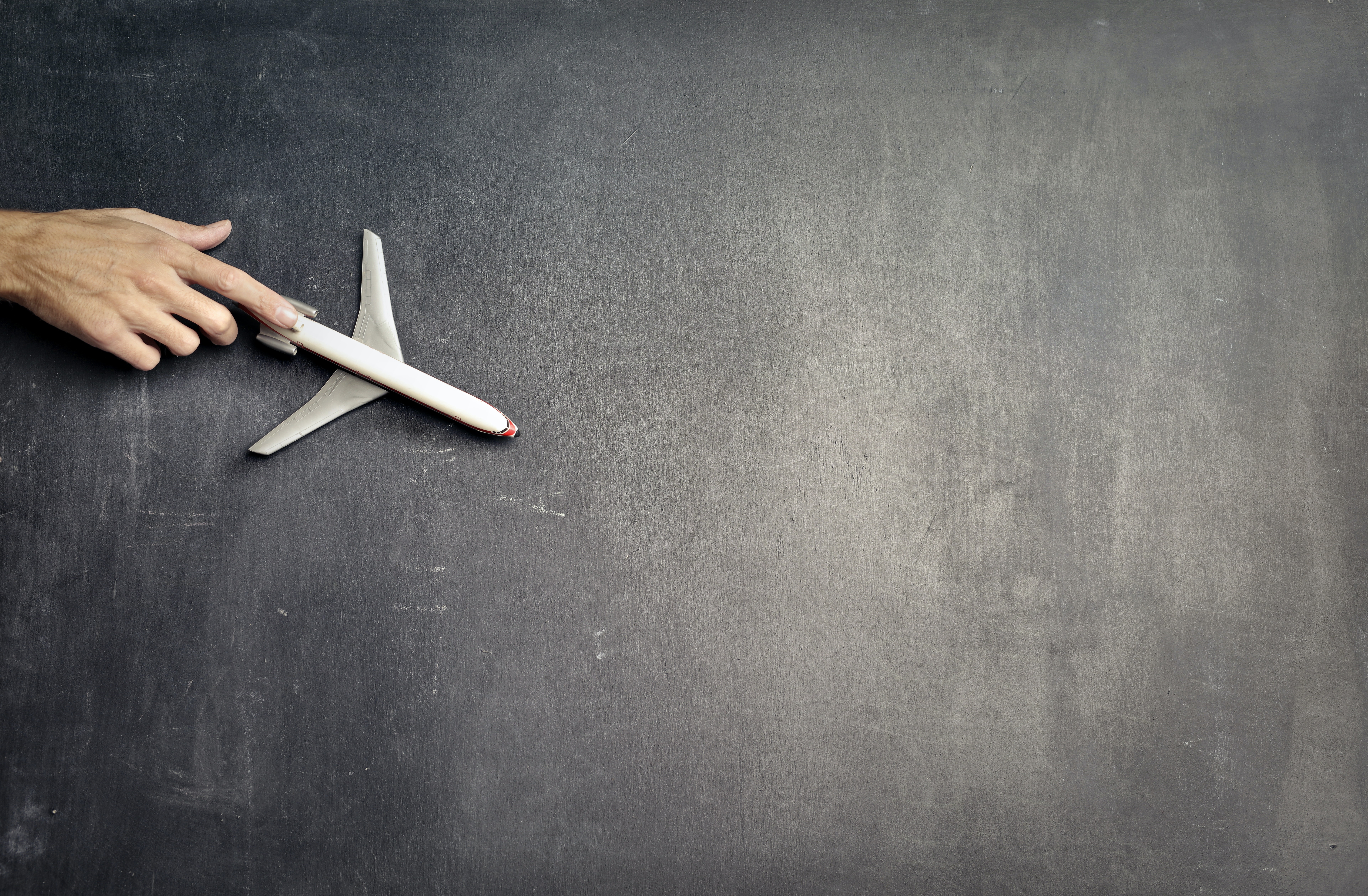 anonymous-person-with-miniature-airplane-on-chalkboard-3769120